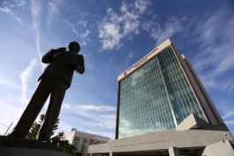 Es una fotografía en la que se muestra el edificio de la Rectoría General de la Universidad de Guadalajara, el cielo está azul y al lado izquierdo aparece la estatua de Constancio Hernández Alvirde